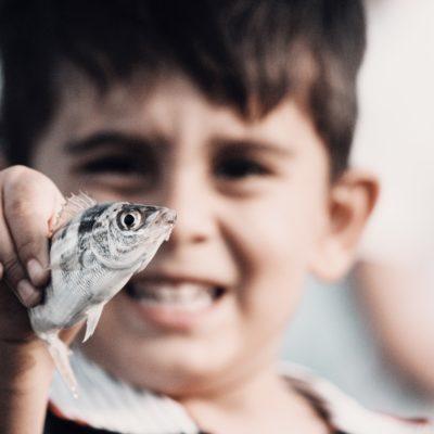 Boy with fish; innocent enthusiasm
